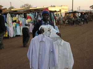 A Malawian man holding several shirts in a market