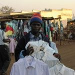 Malawian Man holding shirts at an outdoor market