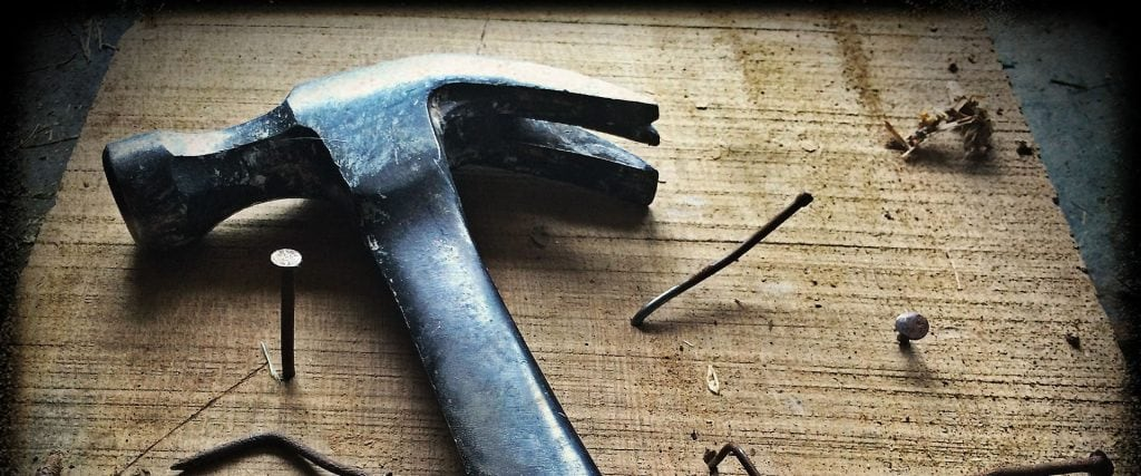 Hammer with nails on a rough hewn wooden board