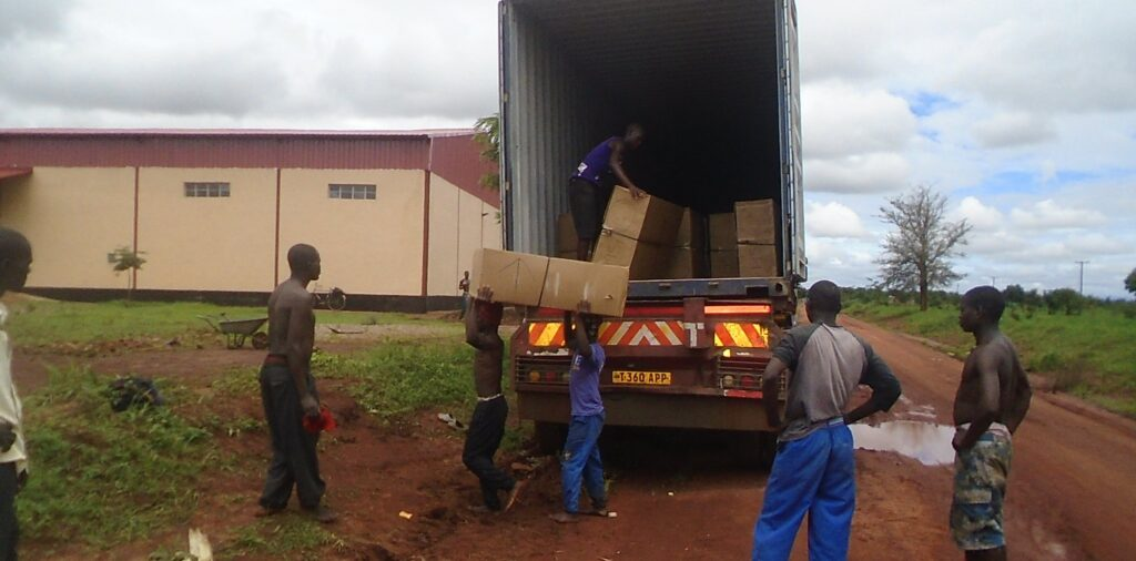 Men unloading supplies from a truck in the rain