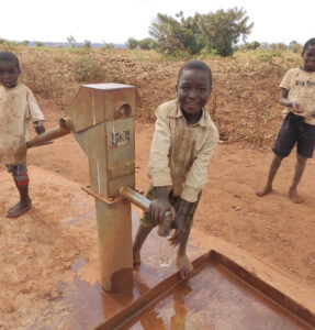 A boy pumping water from a well